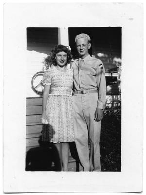 Primary view of object titled 'Couple standing togther outside a home'.