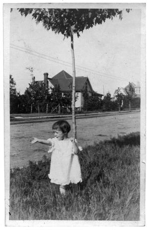 Primary view of object titled 'Child standing in the grass next to a street'.