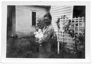 Primary view of object titled 'Man in a military uniform holding a baby in his arms'.