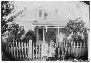 Primary view of object titled 'Theo Scrivner and two children outside a house'.
