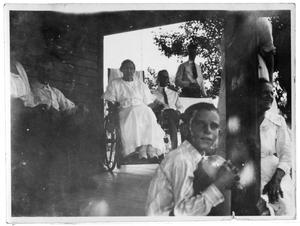 Primary view of object titled 'Group of people sitting together on a covered porch'.