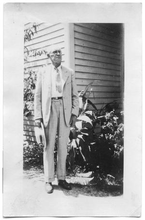 Primary view of object titled 'Henry Scrivner standing outside a house'.