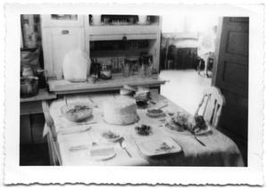 Primary view of object titled 'Dining table with food and place settings'.