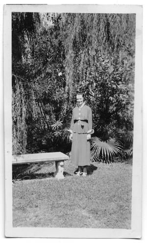 Primary view of object titled '[Unidentfied woman standing beside a bench]'.