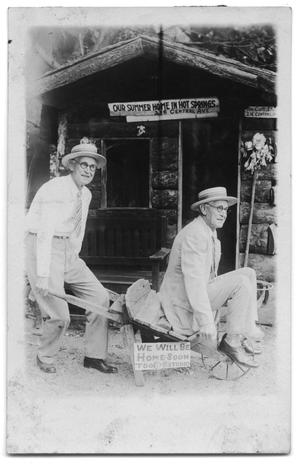 Primary view of object titled 'Postcard of two brothers outside a log cabin'.