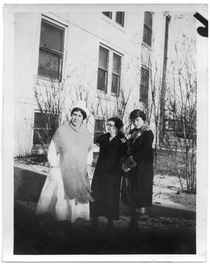 Primary view of object titled 'Three women in winter clothes standing next to a bulding'.