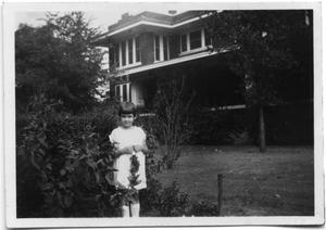 Primary view of object titled 'Clara Jo Vise as a child standing in front of a house'.