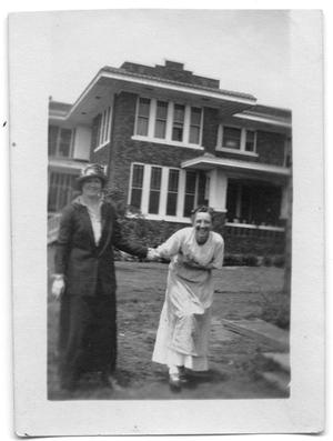 Primary view of object titled 'Sammie Vise and Neely Vise holding hands near a house'.
