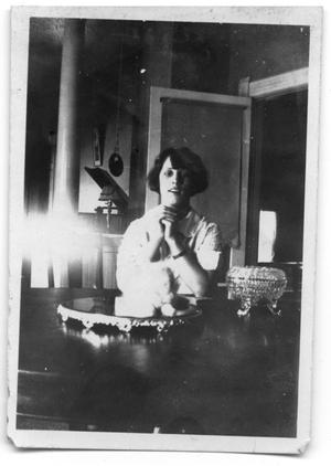 Primary view of object titled 'Unidentified woman sitting at a table'.