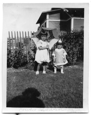 Primary view of object titled 'Two children standing next to a fence in the backyard of a house'.