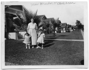 Primary view of object titled 'Mrs. Kruder and two children in the backyard of a house'.