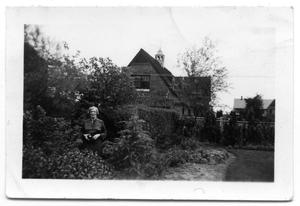 Primary view of object titled 'Sammie Vise standing in the trees outside a stone house'.