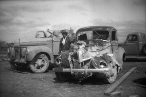 Primary view of object titled '[Man Standing with Damaged Trucks After Tornado]'.