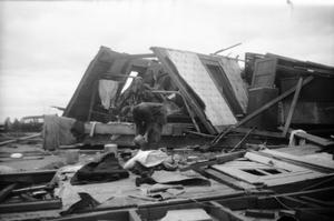 Primary view of object titled '[Photograph of Man and Fallen House After Tornado]'.