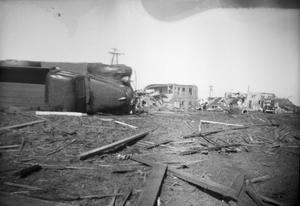 Primary view of object titled '[Photograph of Overturned Truck and Destroyed Houses After Tornado]'.