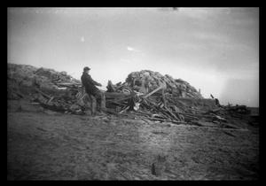 Primary view of object titled '[Photograph of Man and Pile of Debris]'.