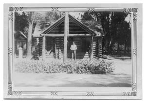 Primary view of object titled '[Man by Log Cabin]'.