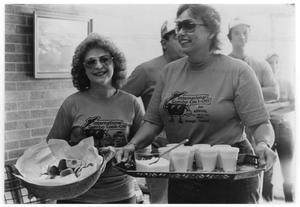 Primary view of object titled 'Two women with serving trays at a Gumbo Cookoff'.