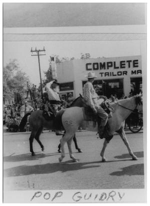 Primary view of object titled '[Pop Guidry Riding a Horse in a Parade]'.