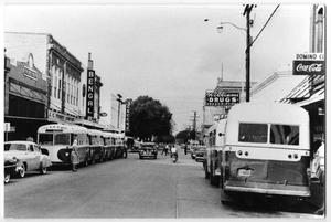 Primary view of object titled 'City buses parked on both sides of a town street'.