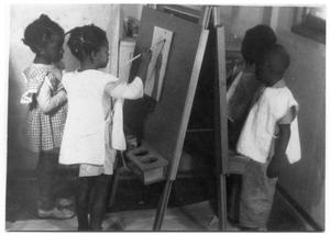 Primary view of object titled '[Four Black Children Painting on an Easel]'.