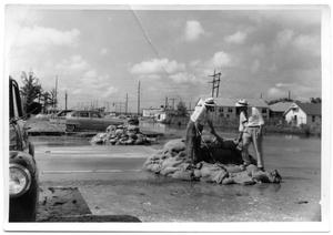 Primary view of object titled 'Two foremen inspect a storm stewer surrounded by sandbags during a 1953 flood'.
