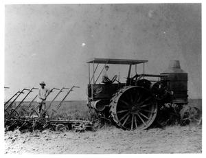 Primary view of object titled '[Two Men Running a Tractor in a Field]'.