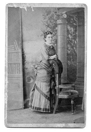 Primary view of object titled '[Elegantly dressed woman posed next to chair]'.