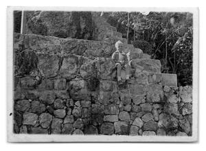 Primary view of object titled '[Child sitting on rocks]'.