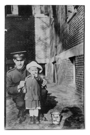 Primary view of object titled '[Child standing next to man in uniform]'.