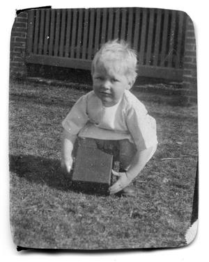 Primary view of object titled '[Young child holding a box]'.