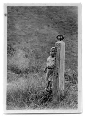 Primary view of object titled '[Child standing next to road marker]'.
