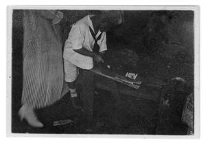 Primary view of object titled '[Boy sawing a piece of wood]'.