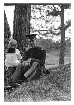 Primary view of object titled '[Man in uniform next to a child]'.