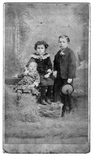 [Three children sitting on hay]