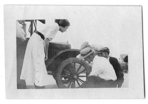 Primary view of object titled 'Several people changing a tire'.