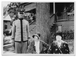 Primary view of object titled '[A man in uniform and two men standing near a tree]'.