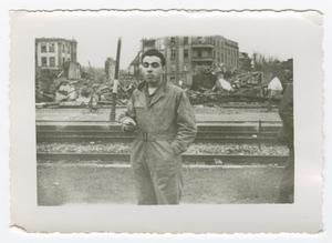 Primary view of object titled '[Man Standing Before Ruined Buildings]'.