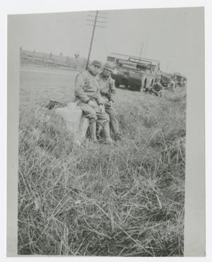 Primary view of object titled '[Photograph of Two Soldiers Sitting Near a Jeep]'.