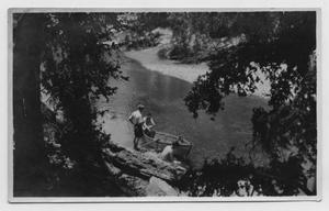 Primary view of object titled '[Three Men Sitting Next to a Canoe]'.