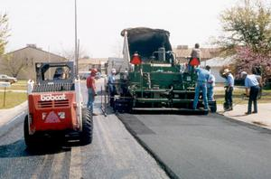 Primary view of object titled '[Unidentified workers surfacing a road in Denton]'.