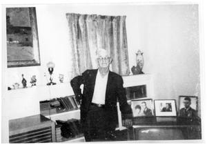 Primary view of object titled '[Wayne Cartledge posing with some of his favorite pictures]'.