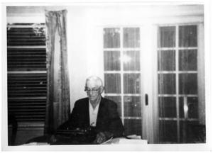 Primary view of object titled '[Wayne Cartledge sitting at a typewriter]'.