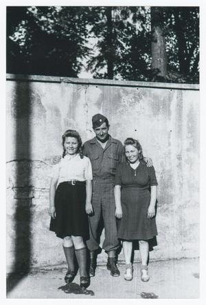 Primary view of object titled '[Frank Rumph Standing with Two Young Women]'.