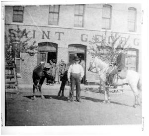 Primary view of object titled '[Two men with two horses in front of the Saint George building]'.