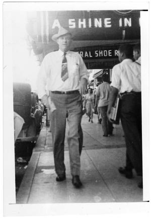 Primary view of object titled '[Henry Allen Coffield on a busy city street]'.