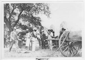 Primary view of object titled '[People Standing Near Covered Wagons]'.
