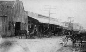 Primary view of object titled '[Blacksmith shop with buggies out front]'.