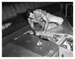 Primary view of object titled 'E.M. Burdine working on a B-58'.