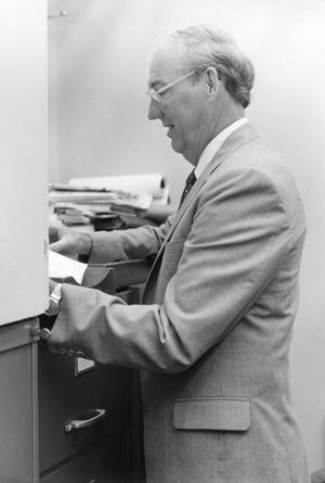 Primary view of object titled '[Photograph of Dr. Fletcher at File Cabinets]'.